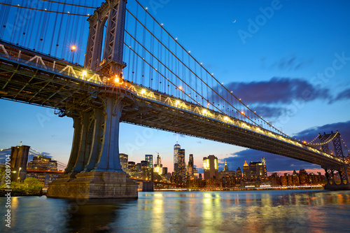 Manhattan bridge and New York City downtown skyline at dusk
