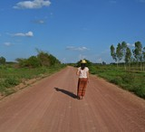 The girl in a brown skirt wearing a hat was walking on a dirt road. The sky is the backdrop