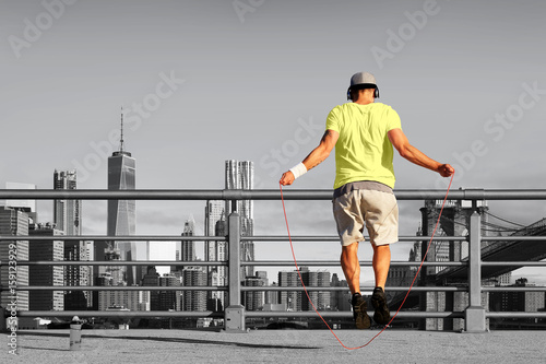 Póster Morning exercises with skipping rope on the background of the city