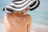 Back view on a beautiful woman in striped hat with sunscreen heart shape on her shoulder having a sunbath on the beach