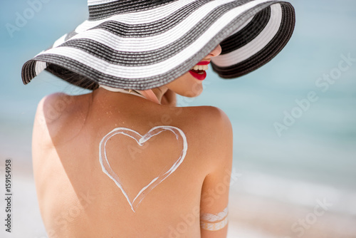 Back view on a beautiful woman in striped hat with sunscreen heart shape on her shoulder having a sunbath on the beach - 159154958