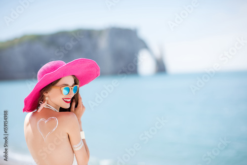 Portrait of a beautiful smiling woman in pink hat with sunscreen heart shape on her shoulder having a sunbath on the beach - 159154988