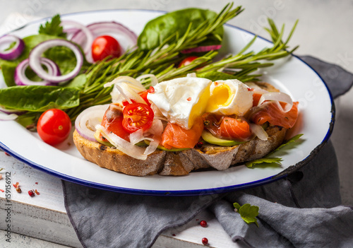 Egg poached and salmon on toast with vegetables. Egg benedict in rustic style. - 159156912