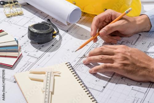 Praca nad planami. Projekt budowlany z narzędziami i notatnikiem.