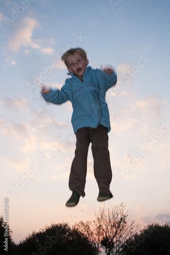 Póster Boy jumping on trampoline
