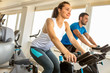 Young man and woman biking in the gym, exercising legs doing cardio workout