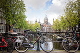 Bikes on bridge over Amsterdam canal, Amsterdam, Netherlands.