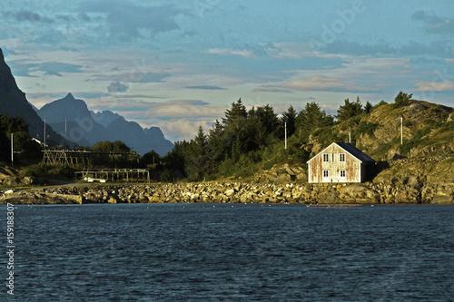 Plagát Dusk over mountains and village on rocky shoreline of Henningsfaer, Norway