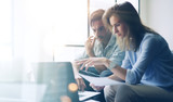 Two young coworkers working on laptop computer at sunny office.Woman holding paper documents and pointing on notebook screen. Horizontal.Blurred background. - 159189547