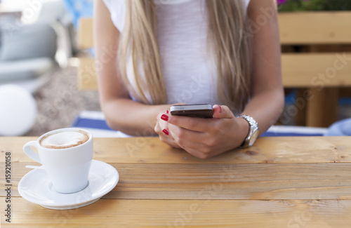 Poster Young woman texting on the phone in a cafe