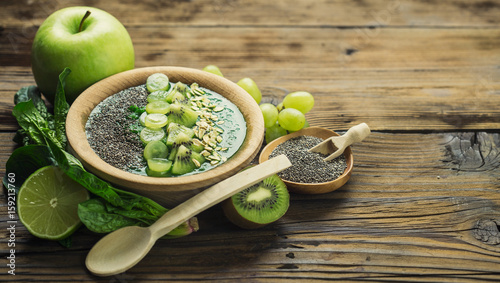 Green smoothie in the bowl with fruits and chia seeds