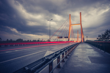 Car light trails on modern bridge during storm - Warsaw, Siekierkowski bridge © tomeyk