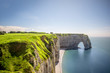 Landscape view on the famous rocky coastline near Etretat town in France during the sunny day. Long exposure image technic with soft water