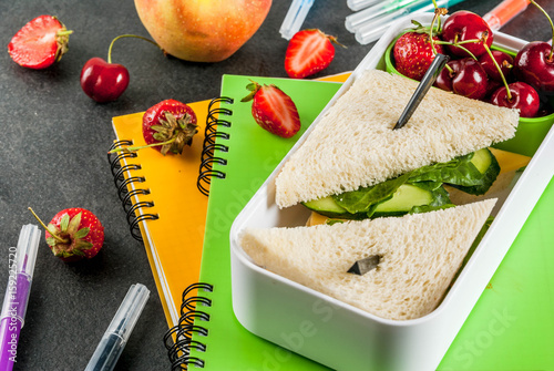 Back to school. A hearty healthy school lunch in a box: sandwiches with vegetables and cheese, berries and fruits (apples) with notebooks, colored pens on a black table. © ricka_kinamoto