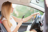 Woman using phone while driving her car - 159241306