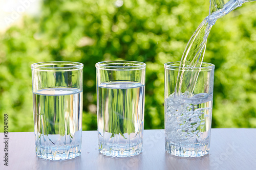 Three glasses of water on a natural background. - 159241989