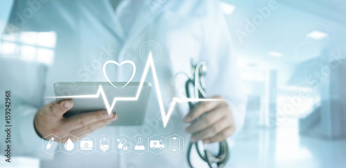 Doctor using digital tablet with medical icon and heartbeat rate in the hospital background © ipopba