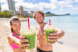 Fitness couple drinking green smoothie at beach. Man and woman holding vegetable smoothies after running sport fitness training. Healthy clean eating lifestyle concept.