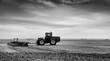 A tractor with attached cultivator working the land in a rural summer black and white countryside landscape