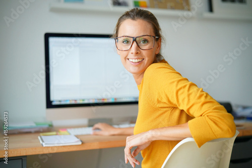 Cheerful trendy girl working on desktop computer - 159264573