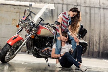Beautiful stylish young couple posing with motorbike in garage