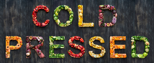 Cold pressed juice vegetables words spelled out with healthy organic fruit on rustic background