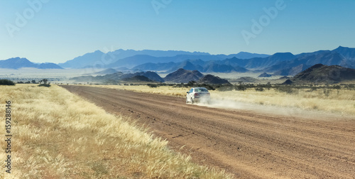 Car driving fast with dust cloud on desert road Poster