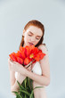 Portrait of a young beautiful woman holding tulips bouquet