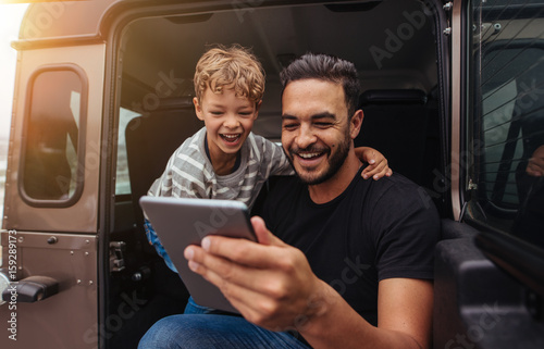 Father and son having fun on road trip with digital tablet Poster