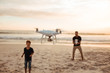 Father and son on summer vacation flying drone on beach