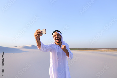Portrait of Arabian sheikh man with gadget that communicates in