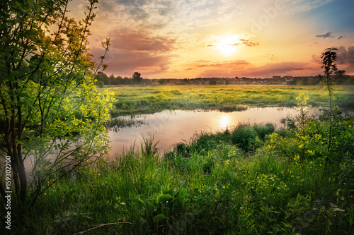 Sunset on the river with green grass and trees on the shore