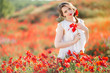 Beautiful girl in field of poppy flowers, spring time