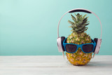 Pineapple with headphones and sunglasses on wooden table over mint background. Tropical summer vacation and beach party concept. - 159312788