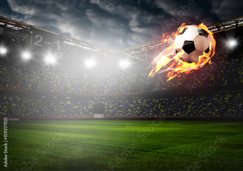 Soccer or football ball on fire at stadium Poster