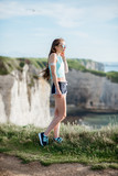 Lifestyle portrait of a woman in sportswear after the training on the beautiful rocky coastline in France