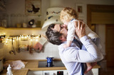 Businessman coming home from work, kissing his little son.