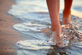 Female feet step on the sea wave