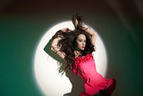 Beautiful brunette woman in beam of searchlight