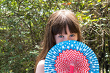 young girl hiding face behind fourth of july fan - 159359789