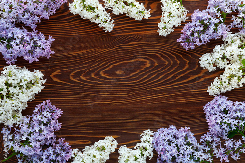 White and purple lilac on a dark brown wood background.