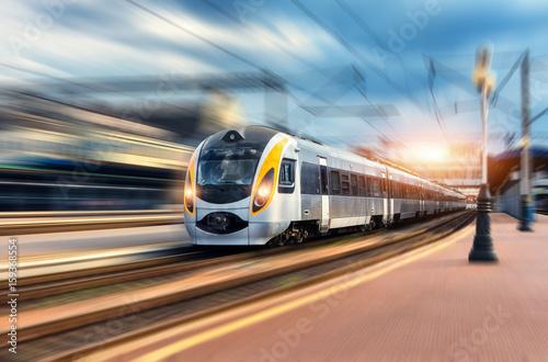 Wysoki prędkość pociąg w ruchu przy stacją kolejową przy zmierzchem. Nowoczesny europejski pociąg intercity na peronie kolejowym z efektem rozmycia w ruchu. Przemysłowa scena z poruszającym pociągiem pasażerskim na linii kolejowej