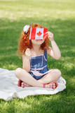Portrait of cute little red-haired Caucasian girl child holding Canadian flag with red maple leaf, sitting on grass in park outside, celebrating Canada Day anniversary