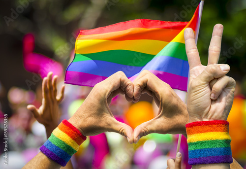 Supporting hands make peace and heart signs in front of a rainbow flag flying on the sidelines of a summer gay pride parade