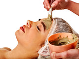 Mud facial mask of woman in spa salon. Massage with clay full face. Girl on with therapy room. Beautician with brush therapeutic procedure isolated background. Healing clay for face.