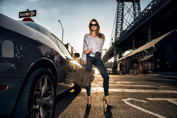 Beautiful fashion model woman posing with a car wearing casual street style outfit