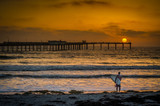 Surfer on California beach at sunset with pier