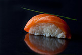 Salmon sushi on a black glossy background.