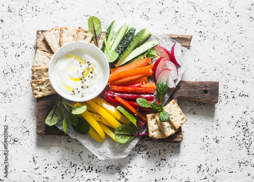 Healthy snack - raw vegetables and yogurt sauce on a wooden cutting board, on a light background, top view. Vegetarian healthy food concept