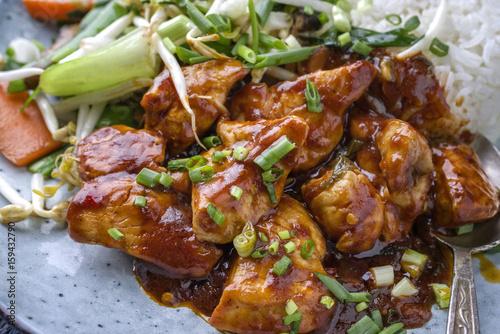 Hühnchen Süß Sauer mit Gemüse und weißen Reis als close-up auf einem Teller